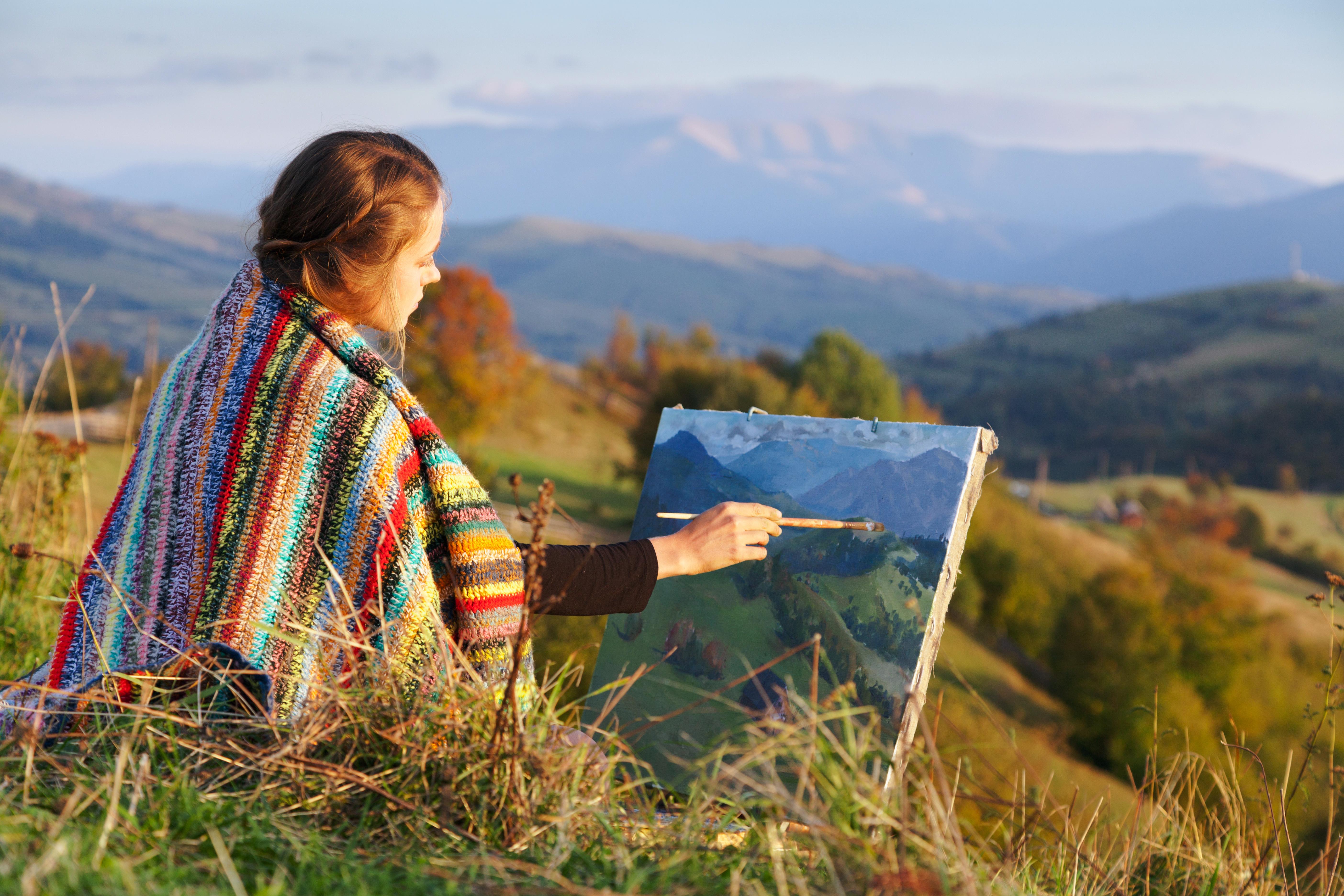 shutterstock_165115982 - female artist painting mtns.jpg